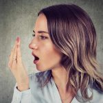 five-ways-to-fight-bad-breath-featured-image-woman-breathing-into-her-hand